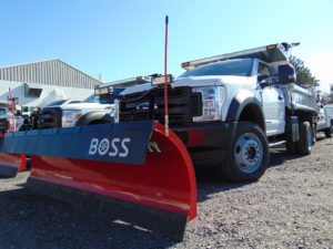 Large snow plow on white work truck