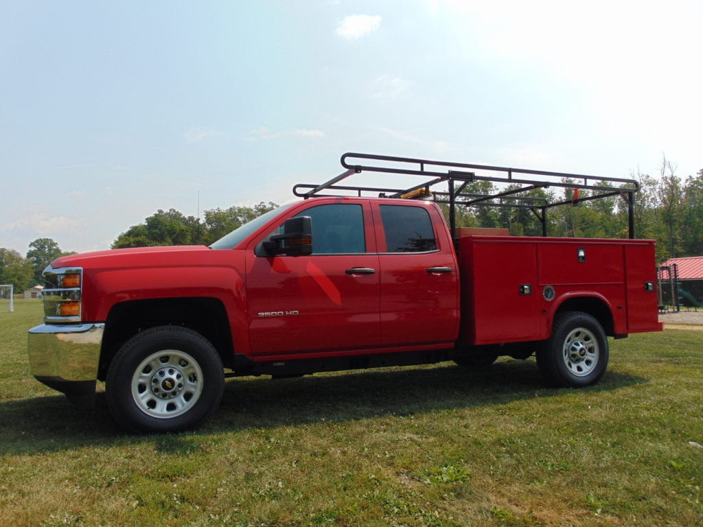 red work truck parked in grass field