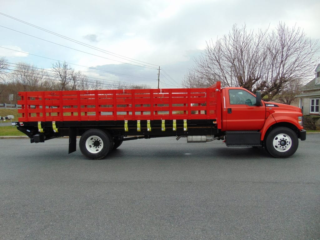 side of red flatbed truck parked on pavement