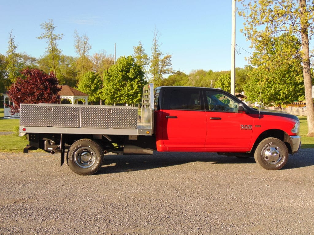 side of red and black flatbed truck parked on gravel