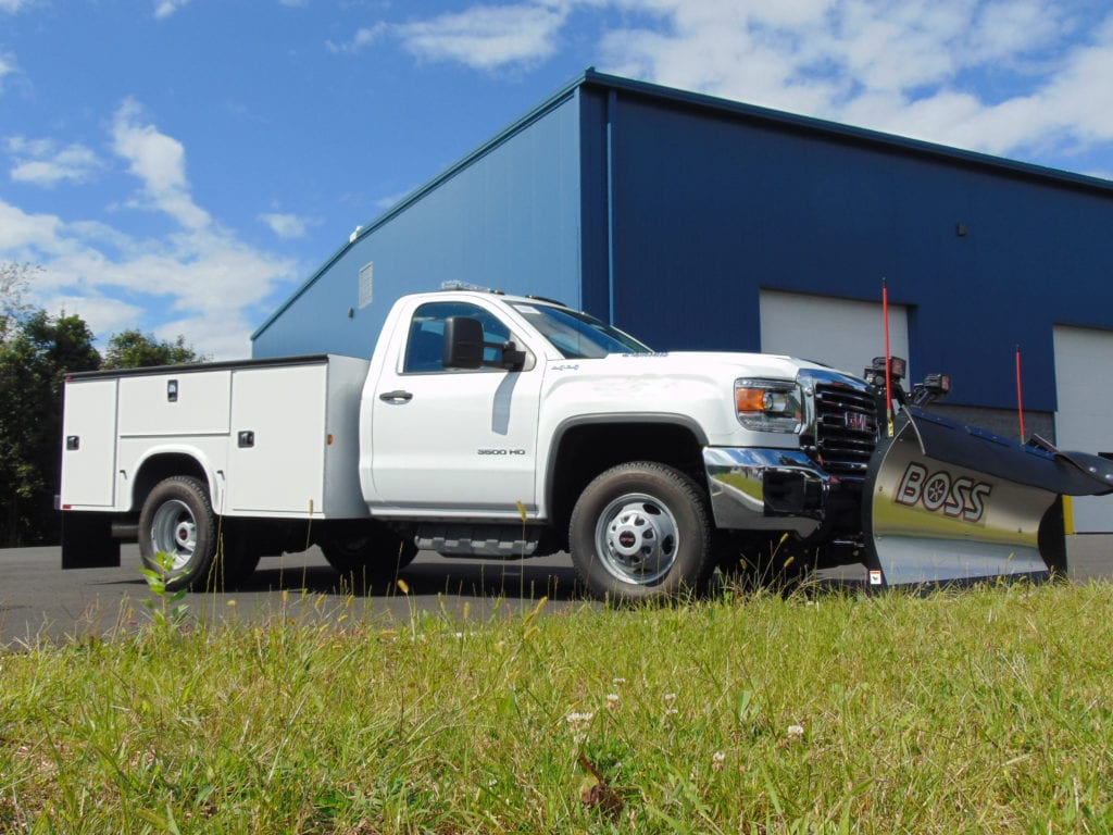 white work truck with plow parked in front of warehouse