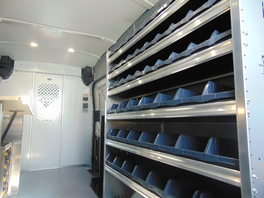 blue shelving in the back of a work van