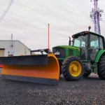 Henke snow plow on green tractor