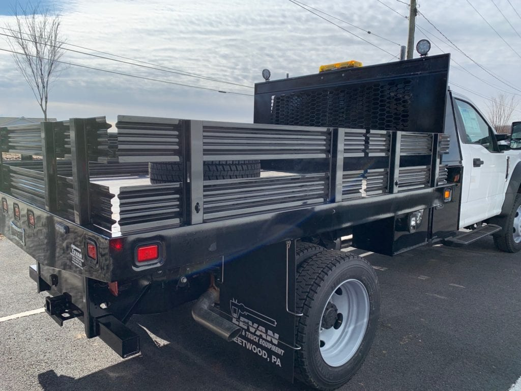 back of black and white flatbed truck parked on pavement