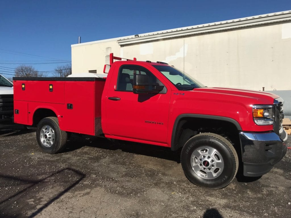 side of parked red work truck on gravel