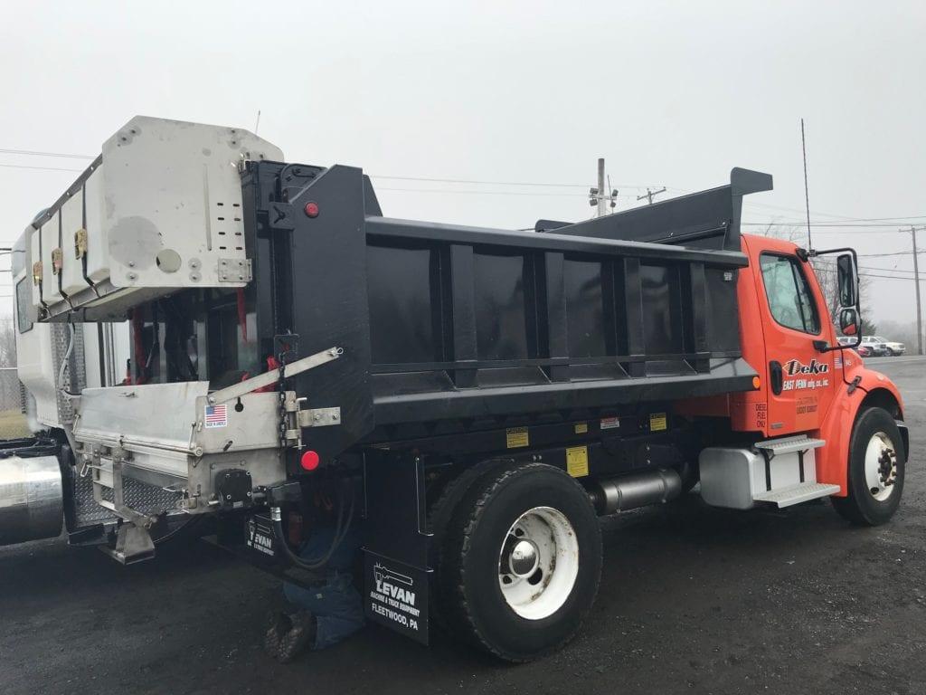side of orange and black dump truck