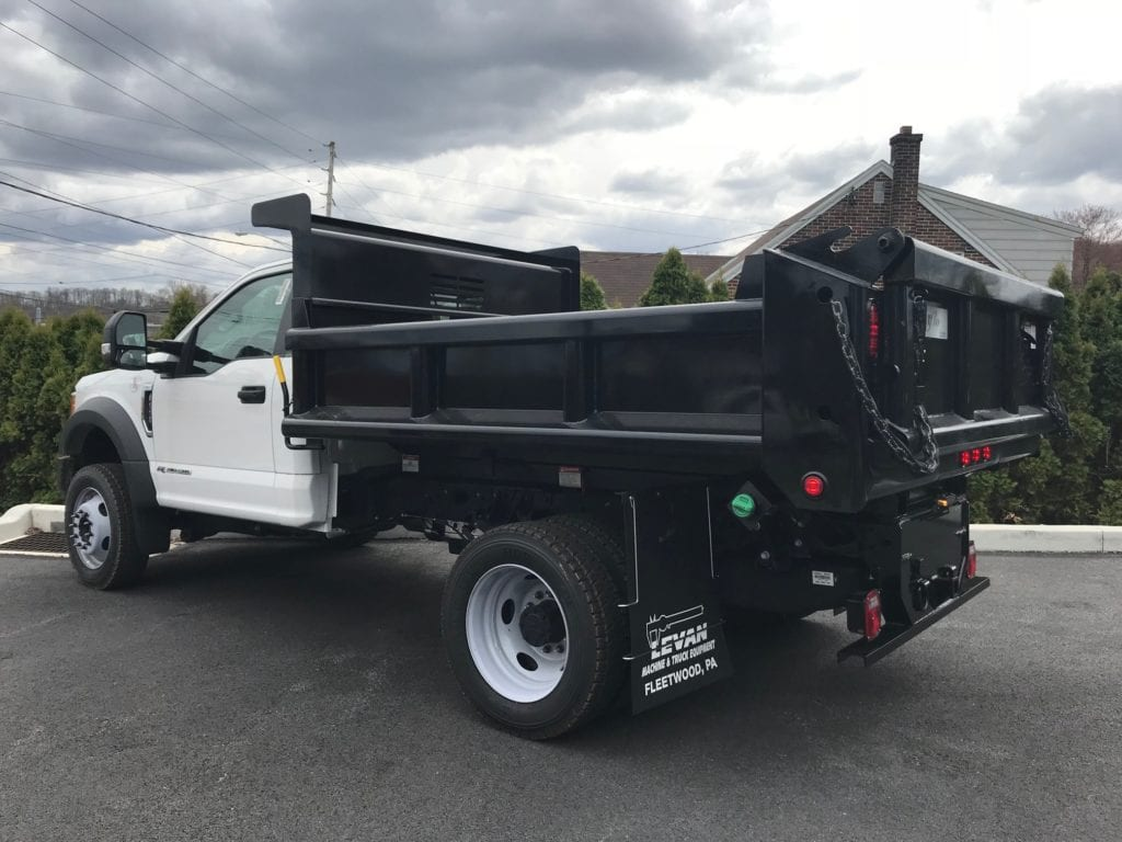 side of black and white dump truck