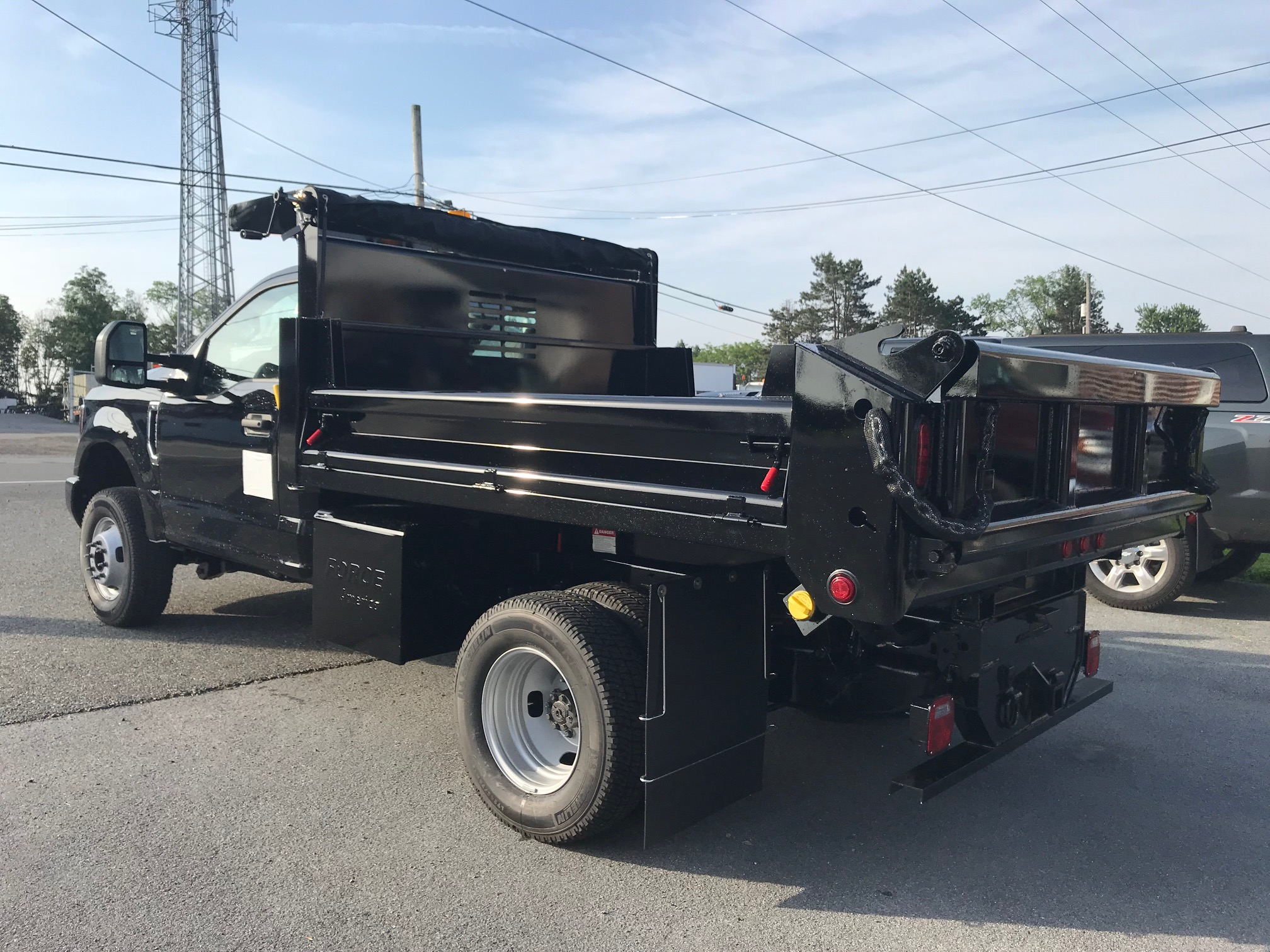 side of black dump truck parked on pavement