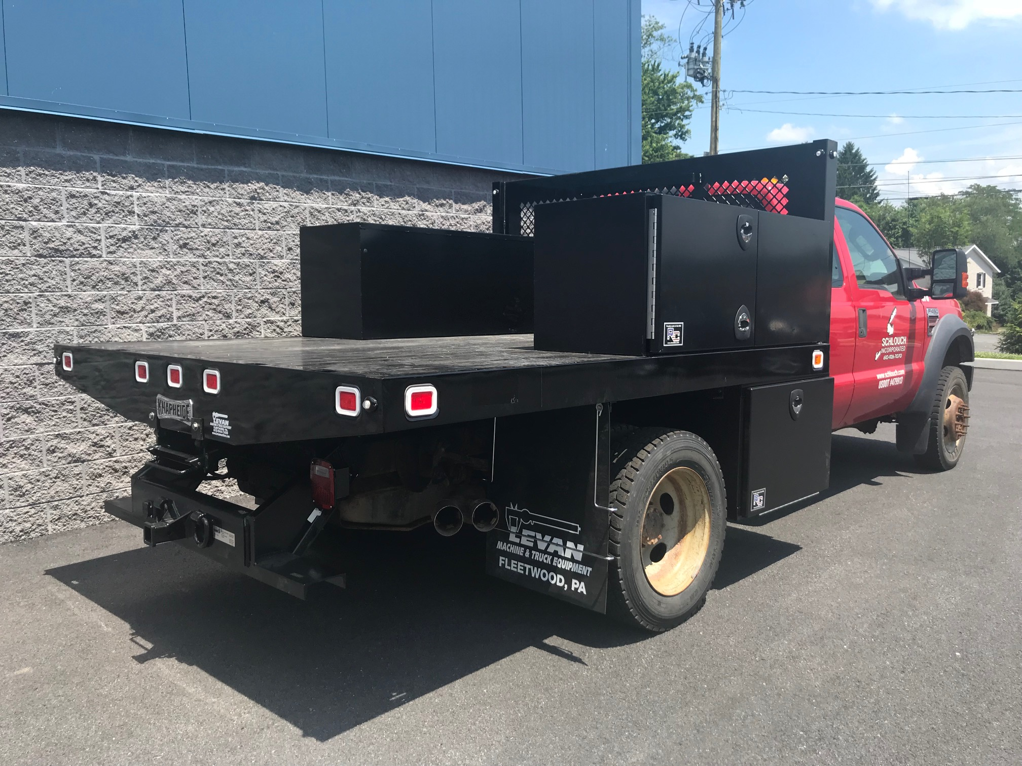 back of black and red flatbed truck with storage containers