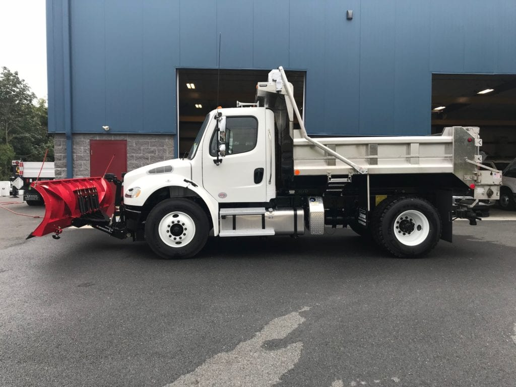 side of white dump truck with red plow