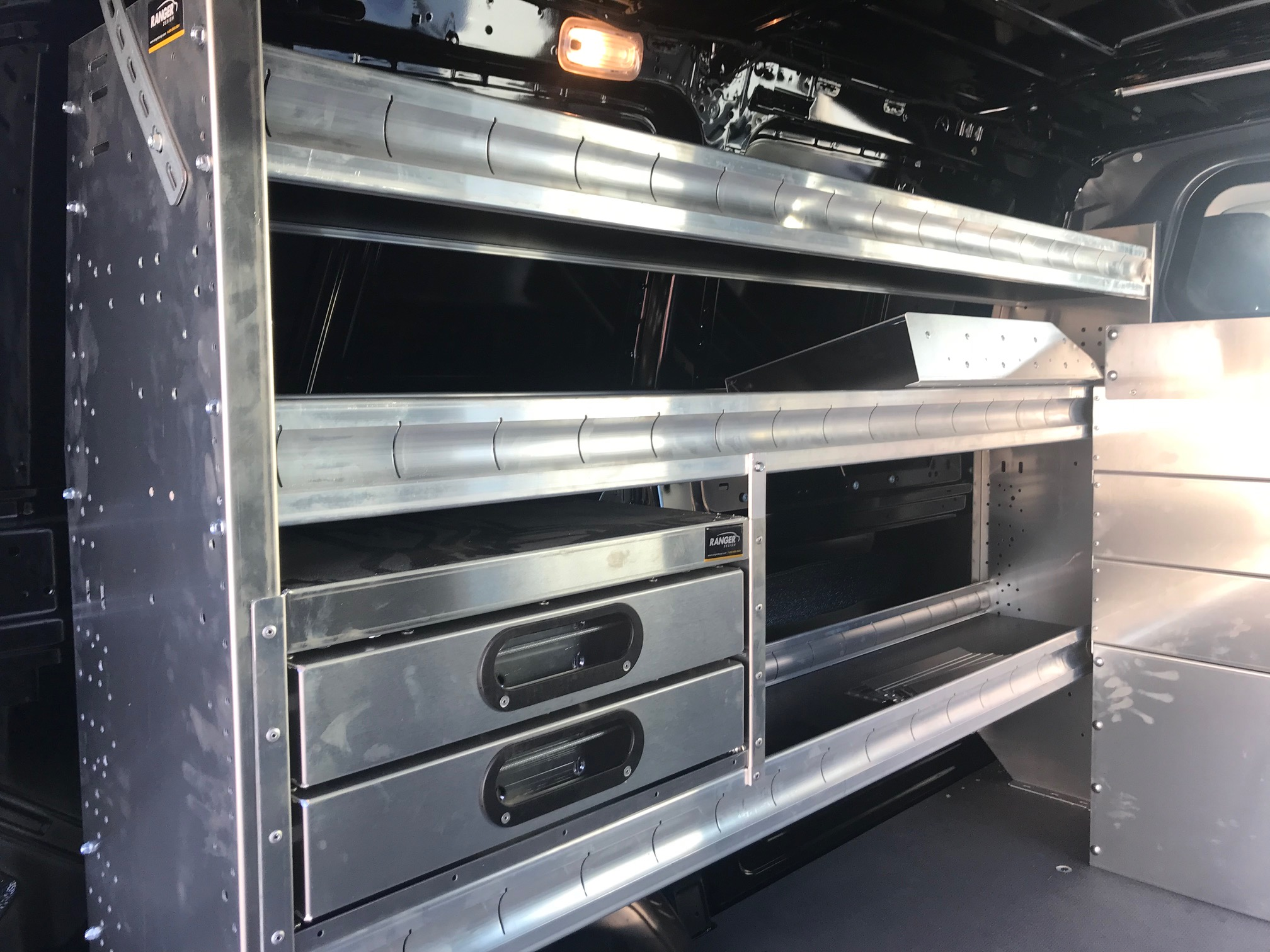 metal shelving and drawers in the back of work van