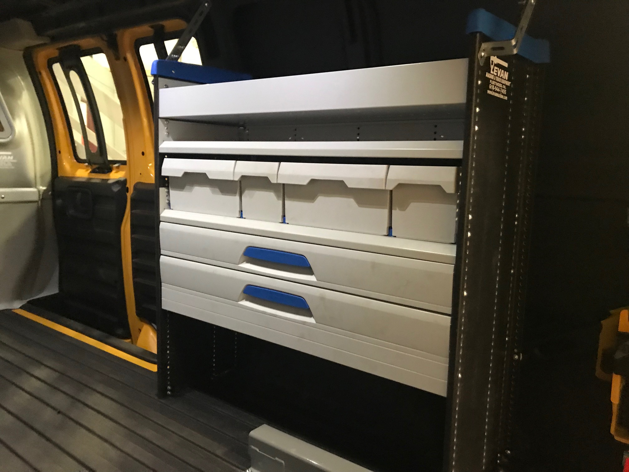 white storage compartments in the back of work van