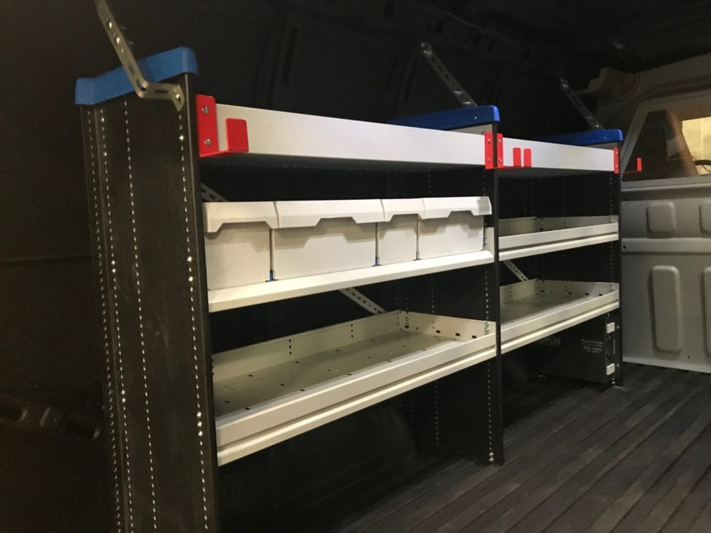 white shelving and storage containers in the back of work van