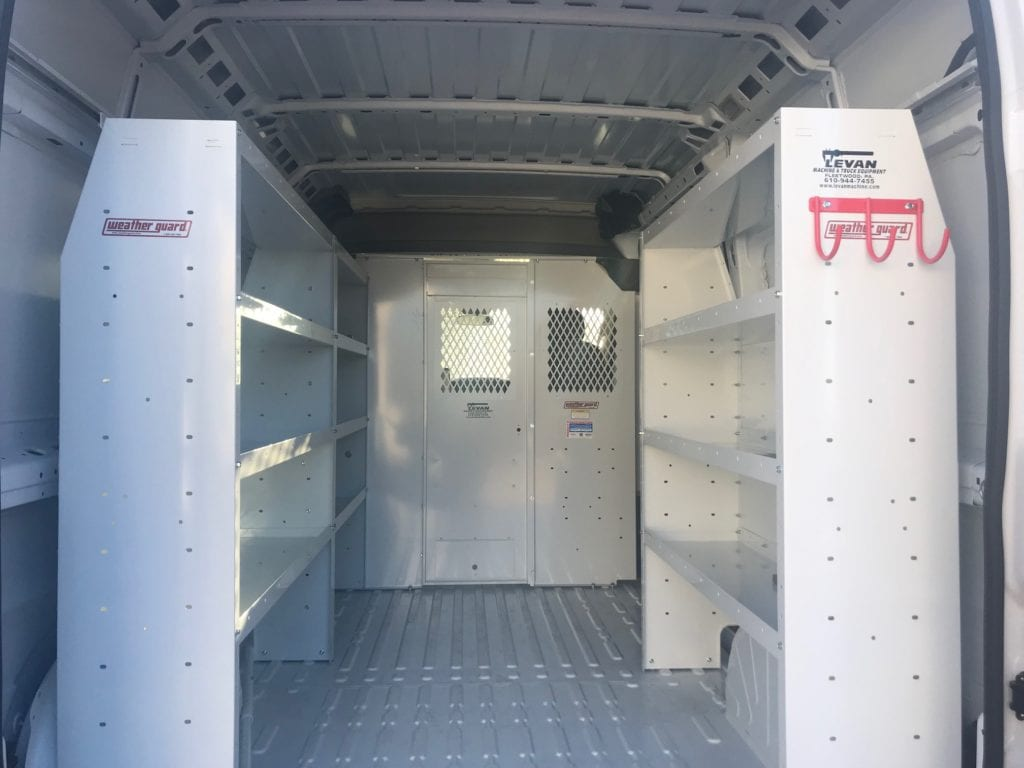 white shelving and red hooks in the back of work van