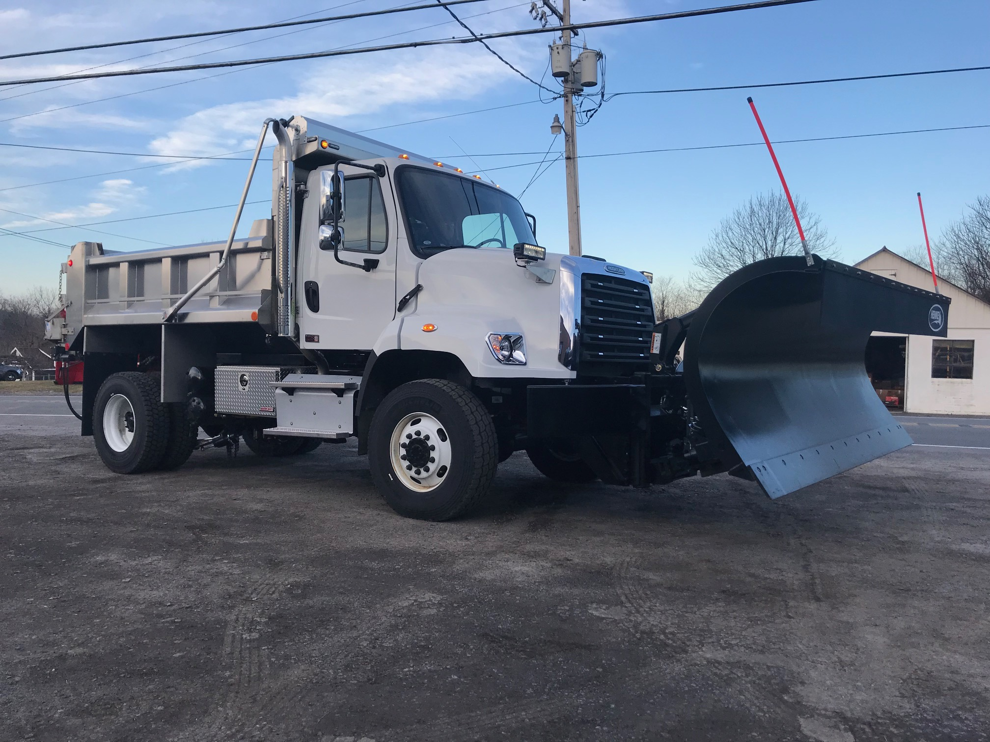 front of white dump truck with black plow