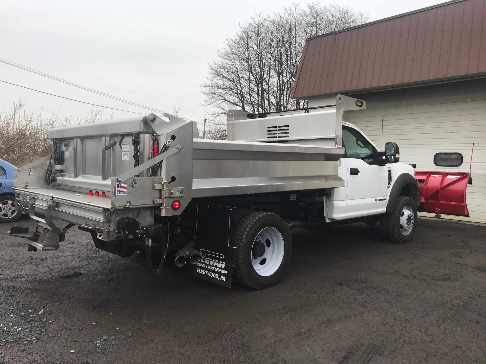 back of white dump truck with red plow