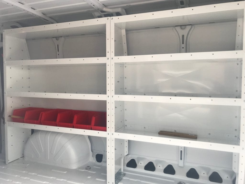 white shelving and red storage containers in the back of work van