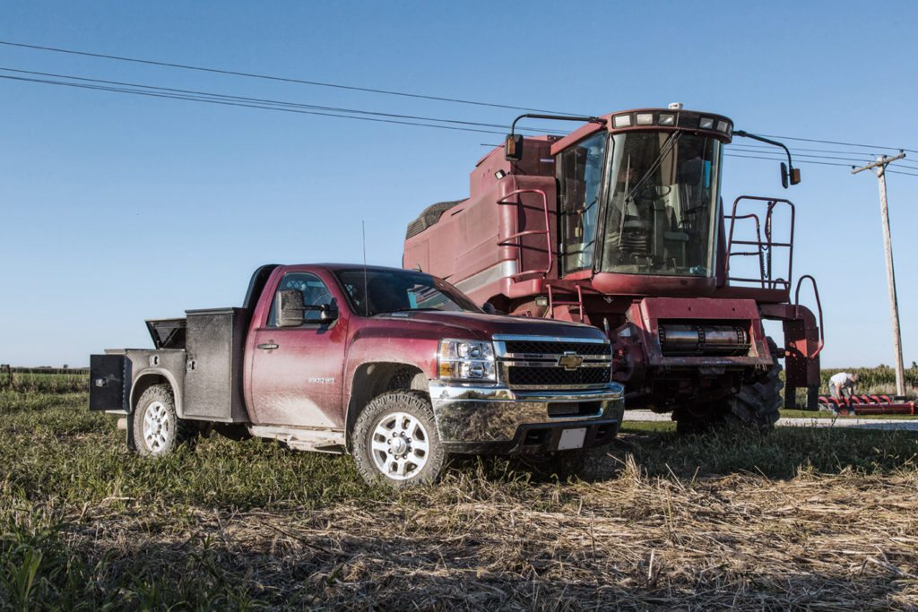 Dark red truck with gooseneck on farm background