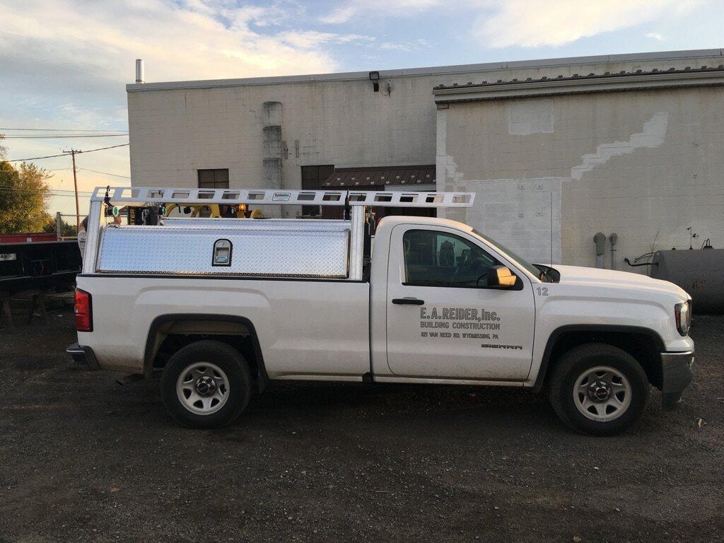 side of white pickup truck parked on gravel