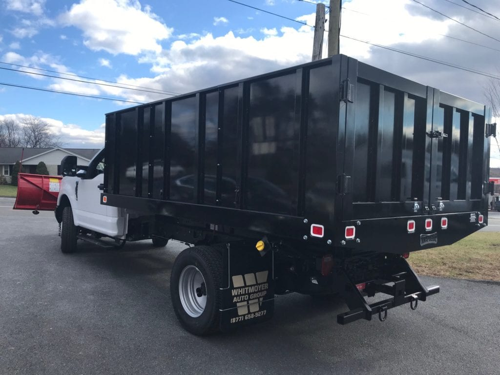 back of black and white flatbed truck with red plow